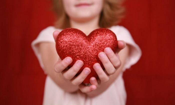 ребенок протягивает игрушечное сердце