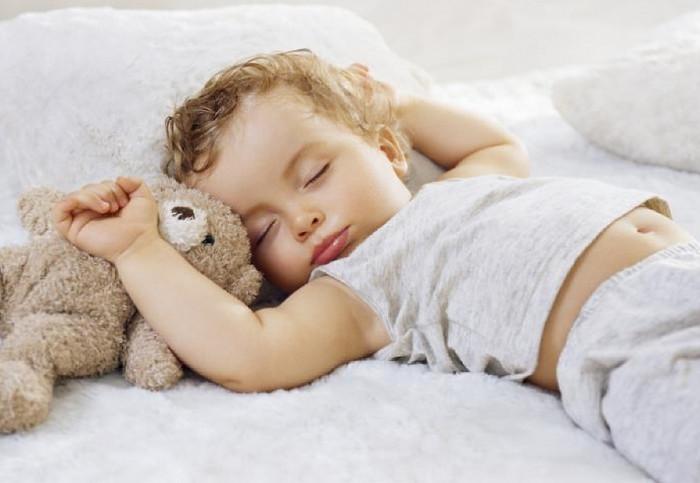 ребенок спит вместе с медвежонком