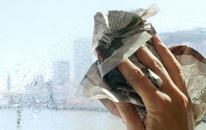 полирует окно газетой