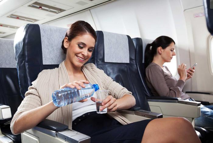 девушка пьет воду в самолете