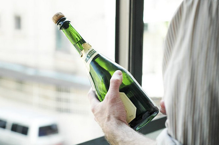 мужчина держит бутылку с вином