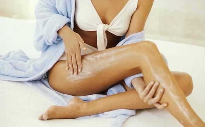 девушка смазывает ноги кремом