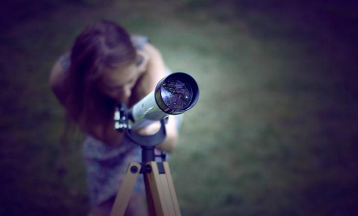 девушка смотрит в телескоп