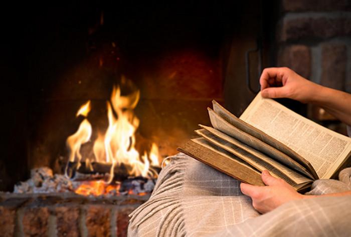 человек читает книгу возле камина