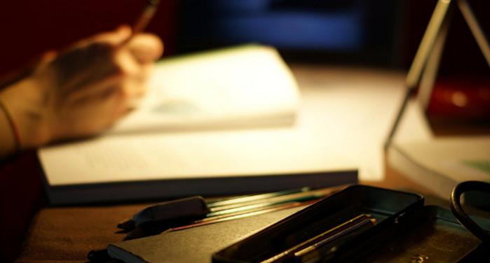 человек пишет при свете ночной лампы