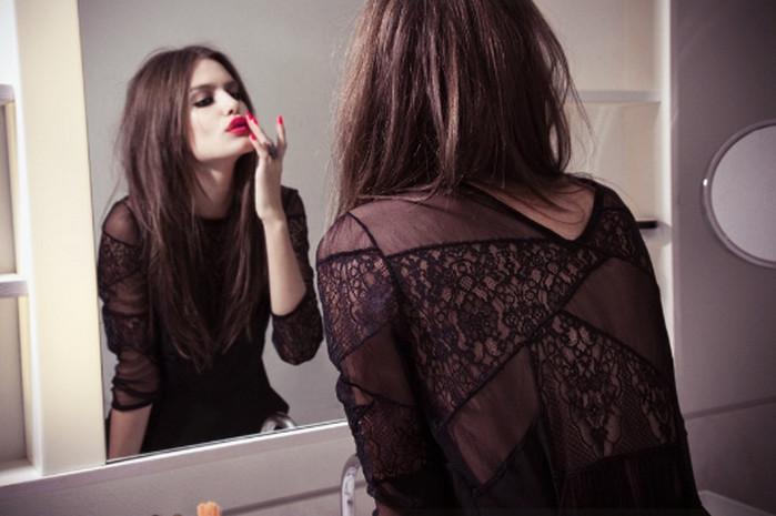 девушка возле зеркала поправляет макияж