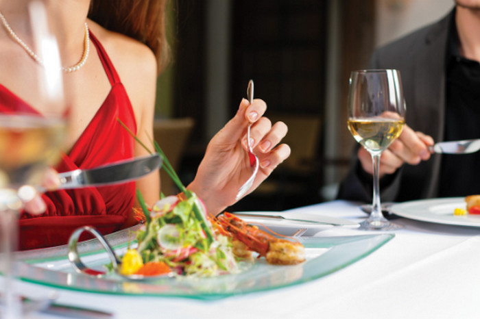 женщина ест, касаясь стола запястьями