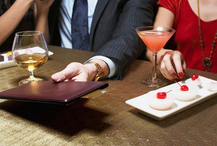 мужчина держит счет за столиком в ресторане