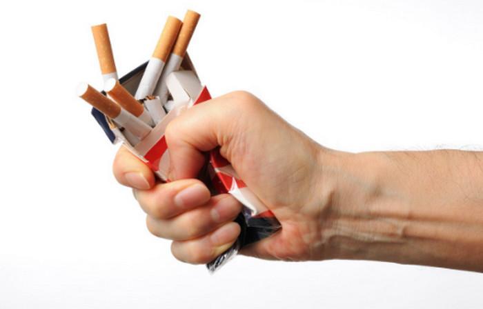 человек сжимает сигаретную пачку