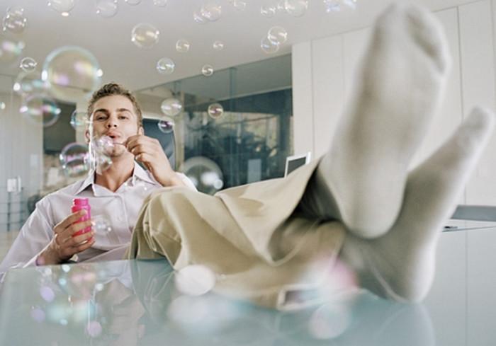 мужчина надувает мыльные пузыри