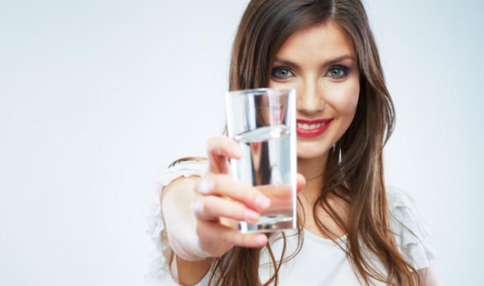 девушка протягивает стакан воды