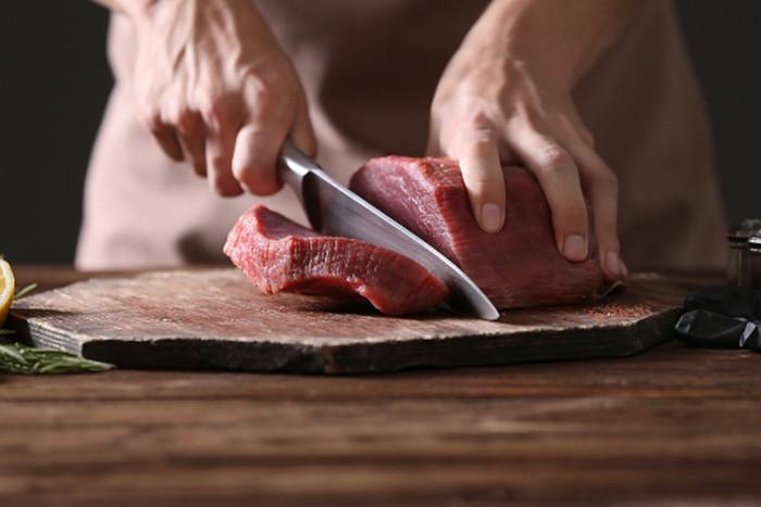 человек режет мясо