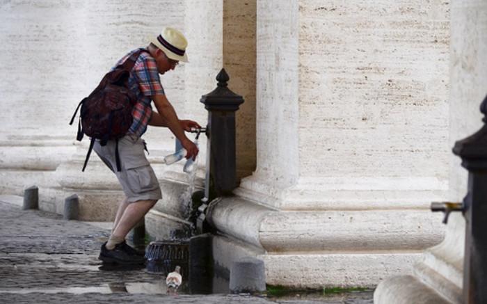 человек набирает воду из фонтана