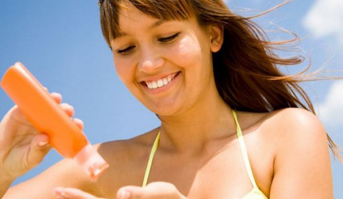 девушка мажется солнцезащитным кремом