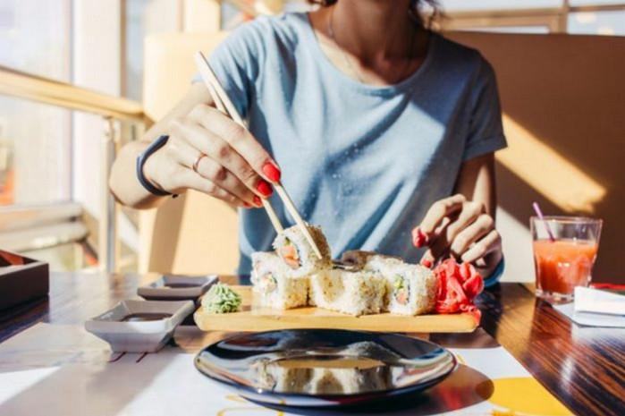 девушка ест суши