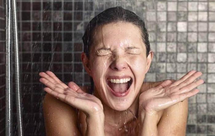 девушка принимает холодный душ