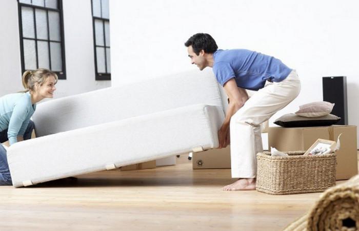 мужчина передвигает диван