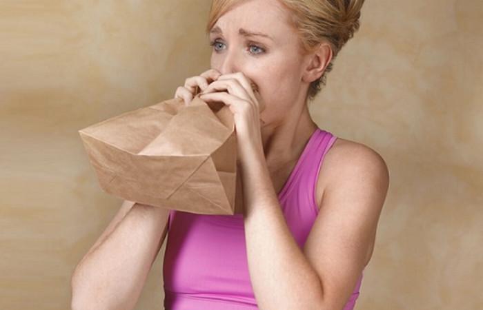 женщина дышит в бумажный пакет