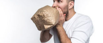 мужчина дышит в пакет