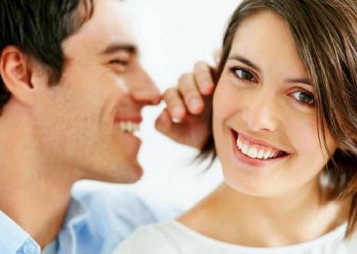 парень говорит что-то приятное на ухо девушке