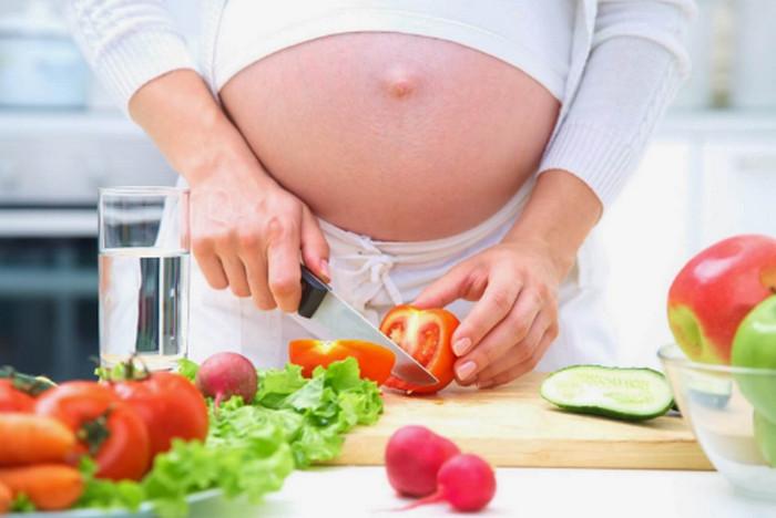 беременная режет овощи