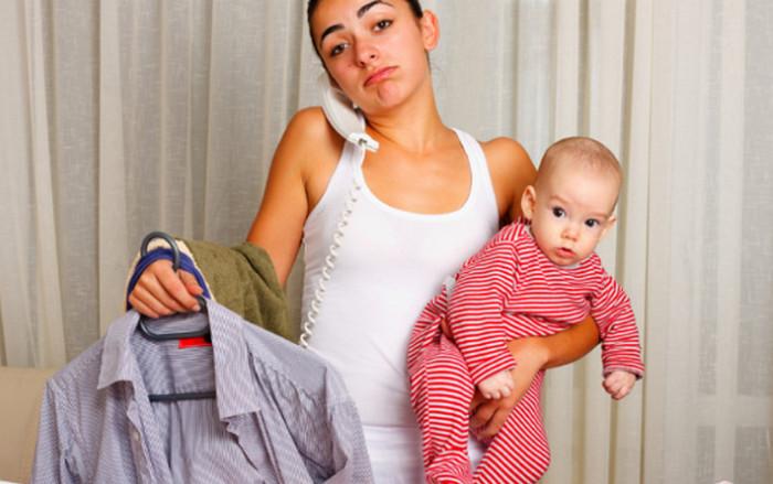 девушка с ребенком на руках гладит рубашку