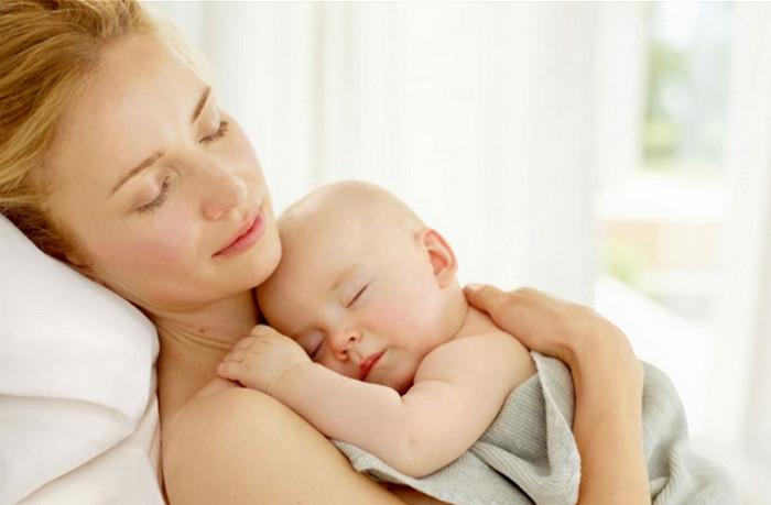 женщина спит с ребенком на руках