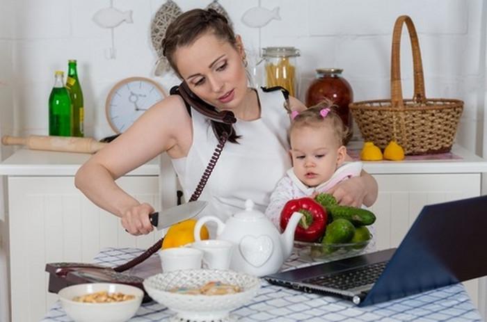 женщина с ребенком на руках готовит еду