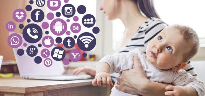 девушка с ребенком на руках смотрит на экран компьютера