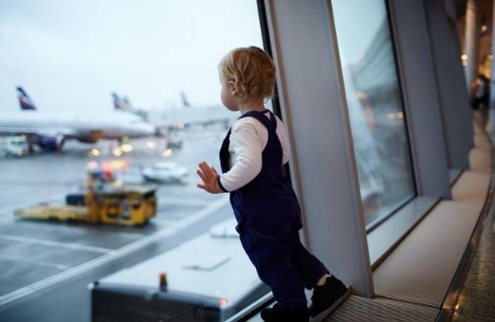ребенок в аэропорту смотрит в окно