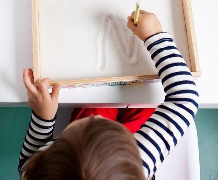 ребенок рисует на сахаре палочкой