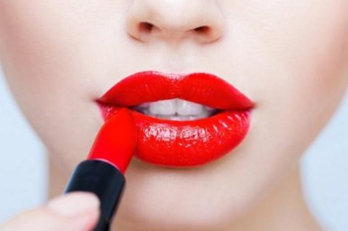 красит губы помадой