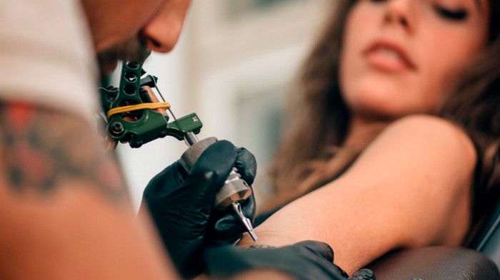 делает татуировку