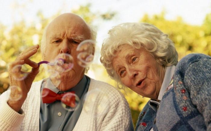 пожилая пара пускает мыльные пузыри