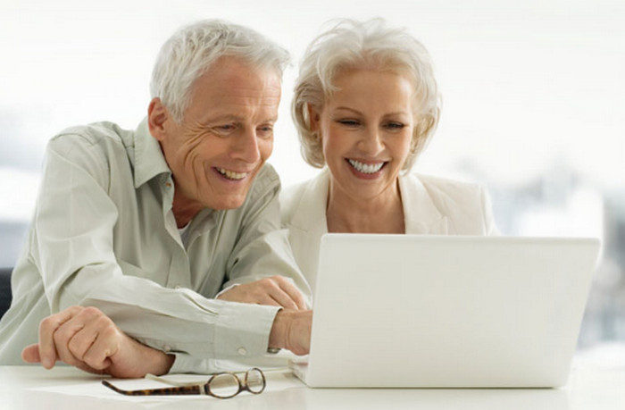 пожилые люди сидят за компьютером