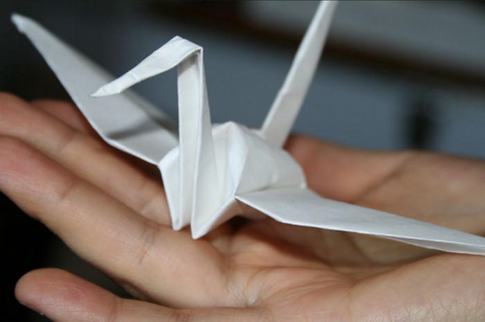 бумажный журавль в руке