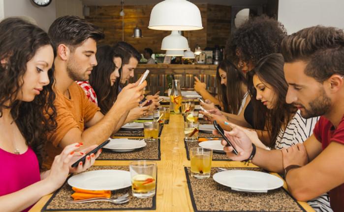 люди сидят за столом со смартфонами в руках