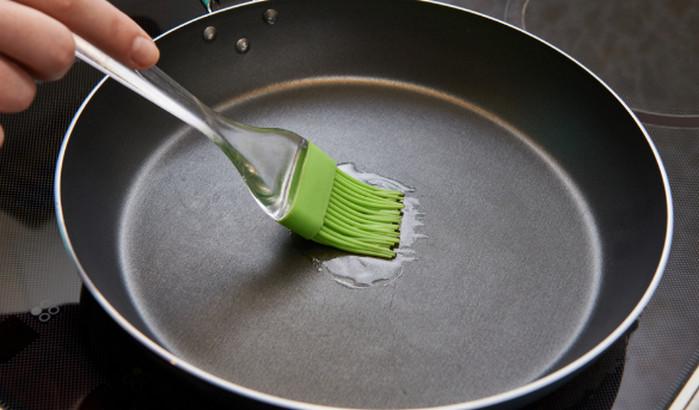 смазывает маслом сковороду
