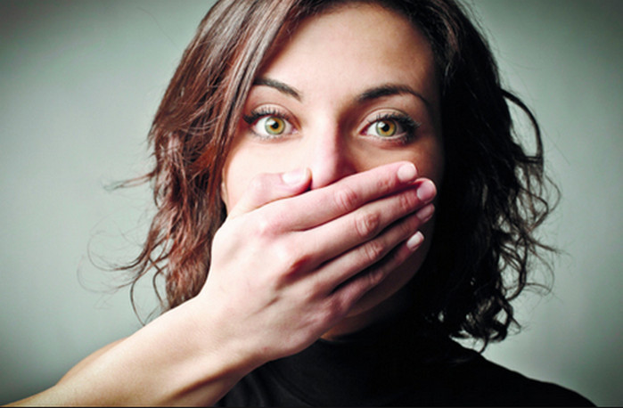 девушка закрывает себе рот рукой