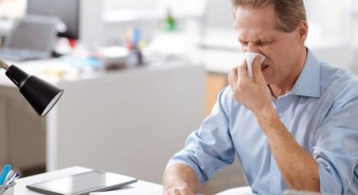 мужчина чихает на работе