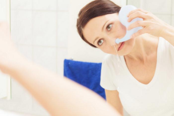 промывает нос водой
