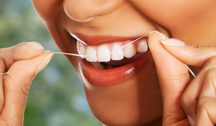чистит зубы зубной нитью