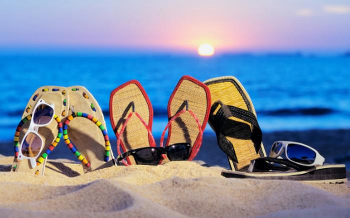 три пары сандалий на пляже