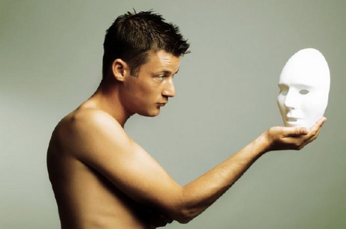 мужчина держит маску