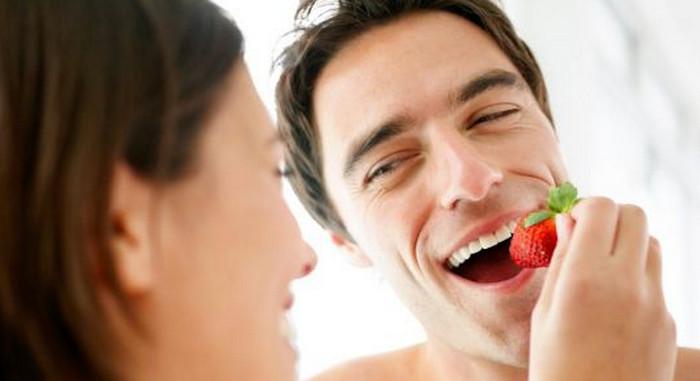 девушка кормит парня клубникой