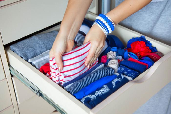 складывает вещи в шкафу