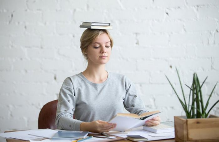 девушка держит книгу на голове