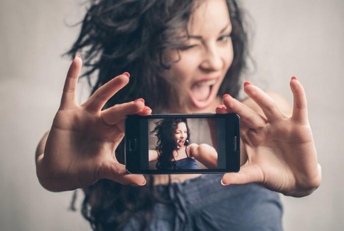 девушка фотографирует лицо вполоборота