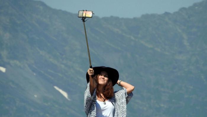девушка делает селфи с палкой