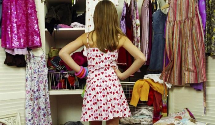 девушка смотрит на шкаф с одеждой
